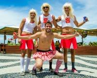 De mannelijke Carnaval-feestneuzen zijn gekleed als vrouwelijke cheerleaders Stock Afbeeldingen