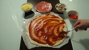 De mannelijke chef-kok smeert rode saus kruidige pizza Ruw deegvoorvormen stock video