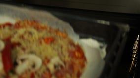 De mannelijke chef-kok zet een bakseldienblad met ruwe pizza in de oven Kokende Pizza stock videobeelden