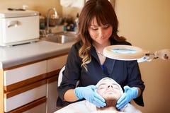 De Mannelijke Cliënt van schoonheidsspecialistapplying cream to in Kliniek Stock Afbeeldingen