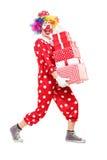 De mannelijke clown die een stapel dragen van stelt voor royalty-vrije stock afbeelding