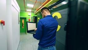 De mannelijke computertechnicus loopt langs de servereenheid stock video