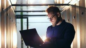 De mannelijke computertechnicus navigeert laptop in een servereenheid stock footage