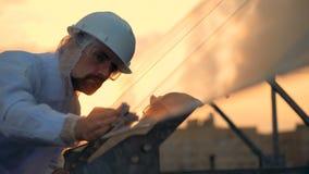 De mannelijke deskundige veegt glasslike oppervlakte van een zonnemodule bij de zonsondergang af stock footage