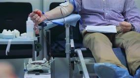 De mannelijke donor schenkt vrijwillig bloed stock videobeelden