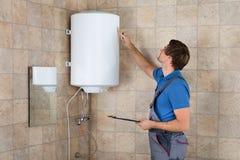 De mannelijke Elektrische Boiler van Loodgieterholding clipboard checking stock afbeeldingen