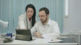 De mannelijke en vrouwelijke artsen bespreken resultaten het gebruiken stock footage