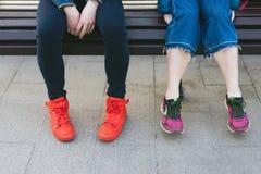 De mannelijke en vrouwelijke benen in heldere tennisschoenen zitten op een bank stock fotografie
