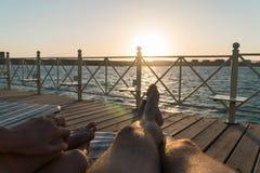 De mannelijke en vrouwelijke benen liggen op een lanterfanter op de pijler bij zonsondergang Stock Foto's