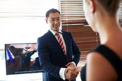 De mannelijke en vrouwelijke ondernemers wensen elkaar met hun succesvol werk geluk Stock Foto's