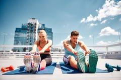 De mannelijke en vrouwelijke vrienden oefenen gelijktijdig op dak uit stock foto