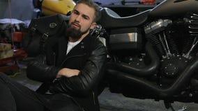 De mannelijke fietser zit op de vloer dichtbij de motorfiets stock video