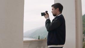 De mannelijke fotograaf let in lens van camera op op landschappen stock videobeelden