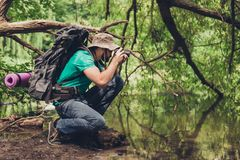 De mannelijke fotograaf is in openlucht dichtbij het meer in het de lentehout, die schot van mooie aard nemen! Hij is een toerist stock foto