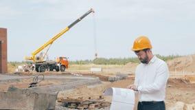 De mannelijke gebaarde bouwwerkgever gekleed in een bouwvakker controleert bouwproces stock video