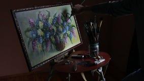 De mannelijke gebaarde kunstenaar in een rode sweater trekt een artistiek borstel het schilderen bloemenstilleven in studio stock video