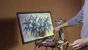De mannelijke gebaarde kunstenaar in een rode sweater trekt een artistiek borstel het schilderen bloemenstilleven in studio stock videobeelden
