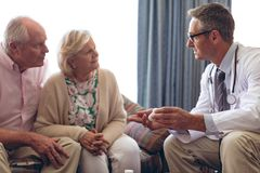 De mannelijke geneeskunde van het artsenvoorschrift aan hoger paar bij pensioneringshuis stock fotografie
