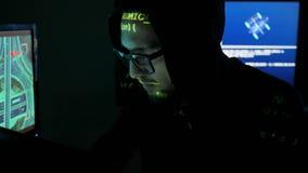 De mannelijke hakker die aan computer, IT professionele programmeur in glazen werken werkt aan computer in het centrum van de cyb stock video