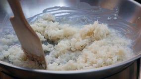 De mannelijke hand beweegt rijst met kokosmelk in wok r Thaise Keuken close-up 4K stock footage