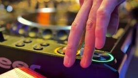 De mannelijke hand controleert de console van DJ De ruimte is verlicht met geel licht stock footage