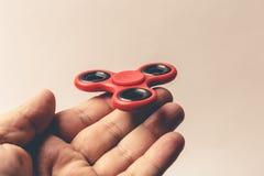 De mannelijke hand die populair rood houden friemelt Spinnerstuk speelgoed op vingers royalty-vrije stock fotografie