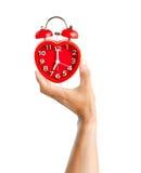 De mannelijke hand die rood klokteken houden bij de klok van 7 o ` betekent kielzog op tijd Royalty-vrije Stock Afbeeldingen