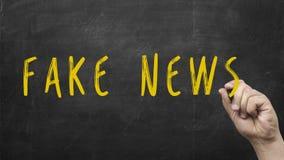 De mannelijke hand die de woorden schrijven vervalst bewust Nieuws op bord als herinnering om zich van hoaxes en desinformatie vo stock fotografie