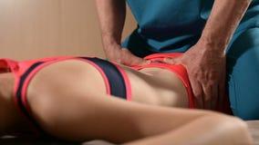 De mannelijke hand diepgewortelde therapeutmasseur behandelt een jonge vrouwelijke pati?nt Het uitgeven van de dij stock footage