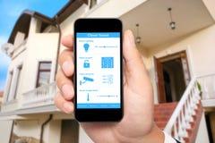 De mannelijke hand houdt een telefoon met systeem slim huis op backgroun royalty-vrije stock foto's