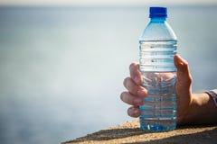De mannelijke hand houdt waterfles op overzeese kust openlucht stock afbeeldingen