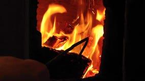 De mannelijke hand met brandpook draait brandend brandhout in oud rustiek baksteenfornuis met open deur stock footage