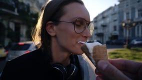 De mannelijke hand met een roomijs die van de wafelkegel zijn meisje voeden, maakt een grap, porde roomijs in de neus, het lachen stock video