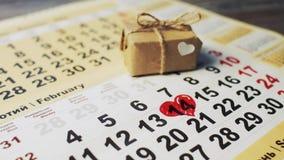 De mannelijke hand met rode teller schildert een hartvorm in de kalender 14 februari dichtbij gift De dag van de valentijnskaart  stock video
