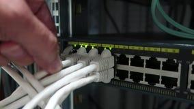 De mannelijke hand neemt de datumkabel in de Internet-router, een close-up op Aanwijzing van verrichting van stock videobeelden