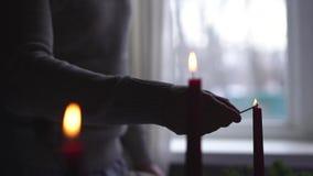 De mannelijke hand op de achtergrond van het venster steekt kaarsen in langzame motie aan stock footage