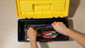 De mannelijke hand opent doos met instrumenten voor reparatie stock video