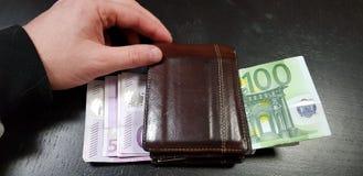 De mannelijke hand raakt een bruin hoogtepunt van de leerportefeuille met euro bankbiljetten stock afbeelding
