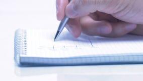 De mannelijke hand schrijft in bedrijfsdocument liggend op de lijst Close-up stock videobeelden