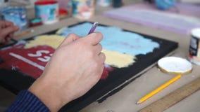 De mannelijke hand trekt brieven met een borstel Gekleurde Achtergrond Art Studio samenwerking Coworking stock videobeelden