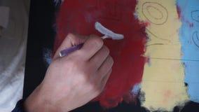 De mannelijke hand trekt brieven met een borstel Gekleurde Achtergrond Art Studio samenwerking Coworking stock video