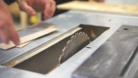 De mannelijke hand trekt houten plakken van timmermansmachine in terug workshop stock videobeelden