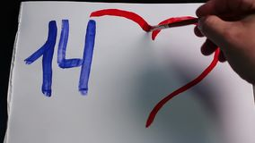 De mannelijke hand trekt nummer 14 en rood hart met zonnige gele stralen op Witboek stock videobeelden