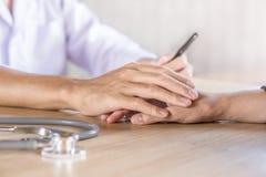 De mannelijke hand van de artsenholding en troostende patiënt in het ziekenhuis royalty-vrije stock afbeeldingen