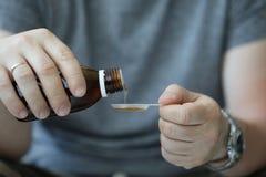 De mannelijke hand van de mens in het ziekenhuis giet hoest stock afbeelding