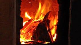 De mannelijke hand zet brandhout en draait brandend brandhout met brandpook in oud rustiek baksteenfornuis met open deur stock videobeelden
