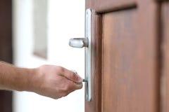 De mannelijke hand zet de sleutel in het sleutelgat Royalty-vrije Stock Fotografie