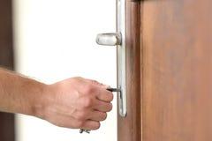 De mannelijke hand zet de sleutel in het sleutelgat Stock Afbeeldingen