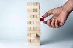 De mannelijke hand zet een kubus op de toren van houten kubussen, als symbool van steun, groepswerk en bedrijfsontwikkeling Horiz royalty-vrije stock fotografie