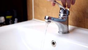 De mannelijke hand zet het water bij de kraan aan stock videobeelden